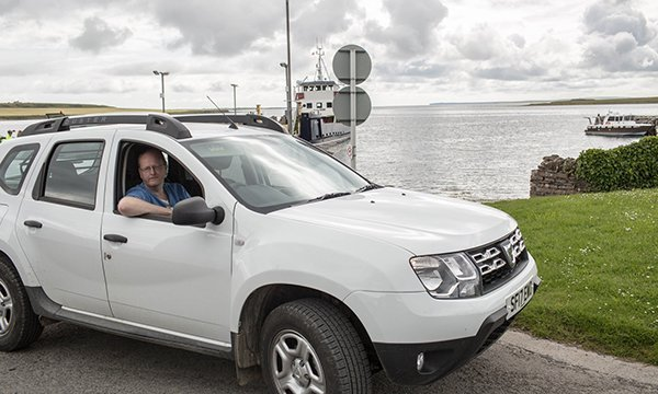 Picture shows Ian Hall, an advanced nurse practitioner at NHS Orkney, in his car at an island harbour. Regional academies for advanced care practitioner roles in Scotland are striving to improve consistency. Picture: QNIS