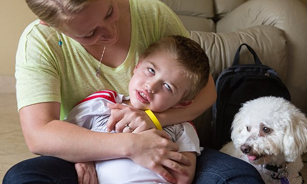 A woman embraces her five year old son, who has been diagnosed with Batten disease
