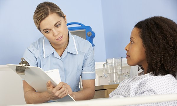 nurse sits by a patient's bedside looking at her clipboard