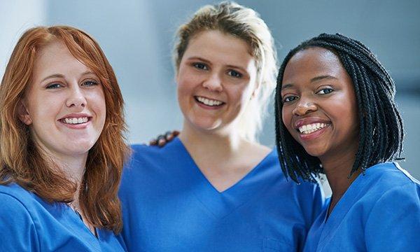 three nurses, dressed in identical uniforms, smiling