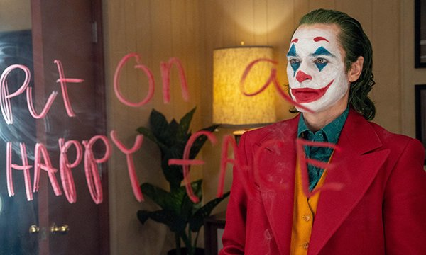 Picture shows a scene from the movie Joker in which the star, Joaquin Phoenix, wearing clown makeup, is looking at a mirror on which has been written, 'Put on a happy face.' The article argues that Joker's portrayal of mental illness is worrying.