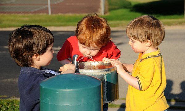 Picture shows boys takingturns drinking from a waterfountain at a park.Practical information aimed at schools, nurseries and colleges to support children with bladder and bowel issues and toileting has been published by Bowel and Bladder UK.