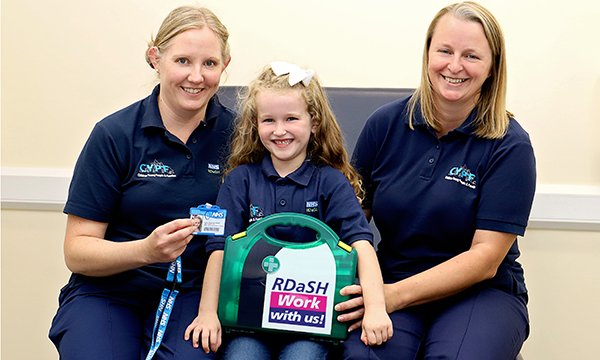 Picture of Nahla Walker (centre), with nursesHelen Drury (left) and Joanne Leivesley. When Nahla, aged six, told them she wanted to be a nurse, they ordered a special outfit for her with the name badge 'Nurse in training'.