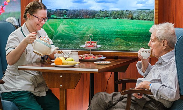 Occupational therapist Anna Tilney takes tea with a patient, who is dressed in his day clothes