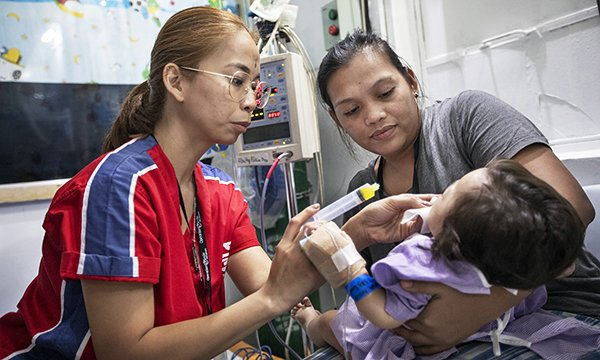 Operation Smile nurse Clark Agno-Gonzales treats a child held by a woman in Cebu, Thailand