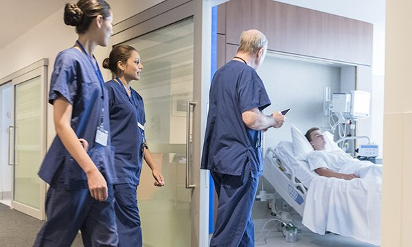 Nurses following a doctor into a hospital room with a patient. Picture: iStock