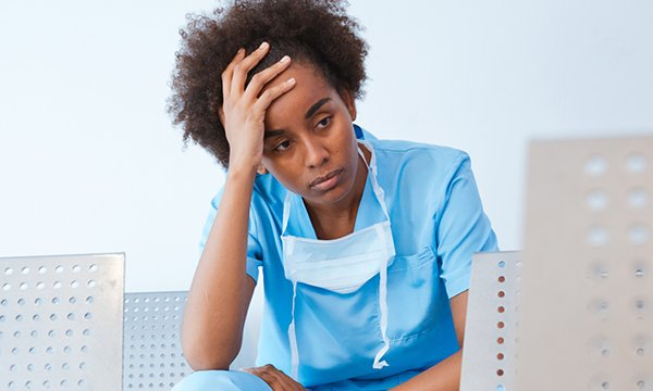 Picture shows a young nurse in scrubs looking weary with her hand to her head. Added stress from the coronavirus and helping patients to cope with an uncertain future is stretching the resilience of nurses.