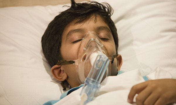 Image of a child in a hospital bed with an oxygen mask